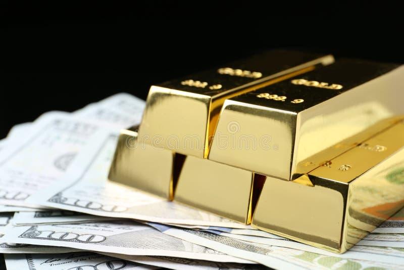 Shiny gold bars and money on black background. Closeup royalty free stock photo