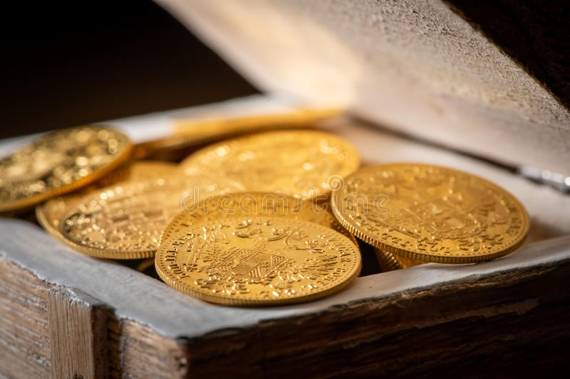 Gold coins in a small wooden box. Shiny gold coins Austrian ducats in a small wooden treasure box royalty free stock image
