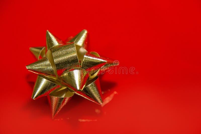 Shiny gold satin ribbon on red background. royalty free stock photos