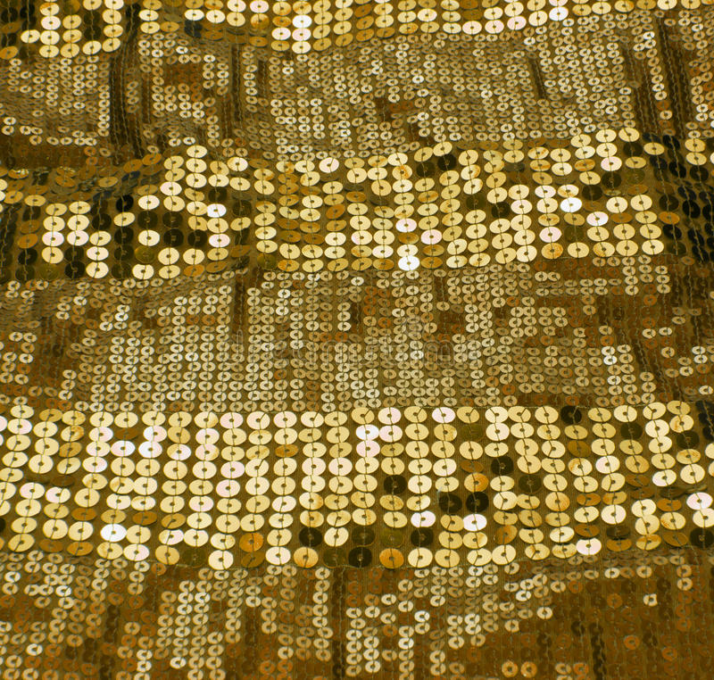 Gold sequin. A shiny gold sequin background stock photo