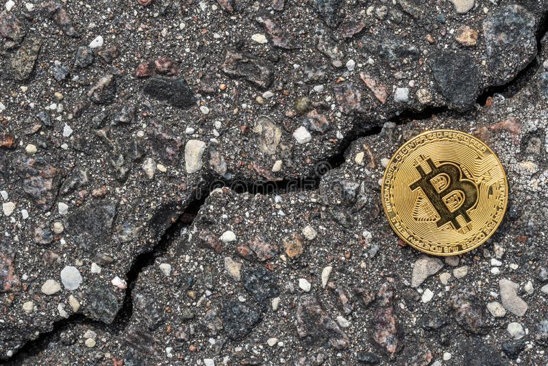 Shiny golden bitcoin on cracked asphalt royalty free stock image