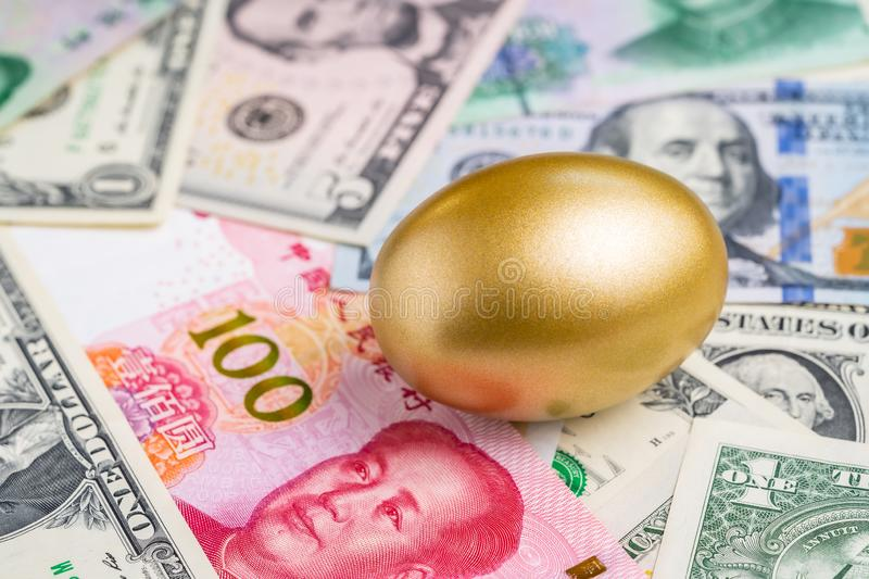 Shiny golden egg on pile of Chinese Yuan and US America dollar banknotes money metaphor of finding the good stock with high royalty free stock photo