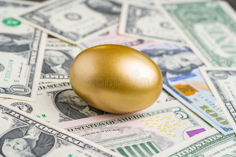 Shiny golden egg on pile of US America dollar banknotes money metaphor of finding the unbelievable good stock with high dividend. Or success investment in stock stock photo