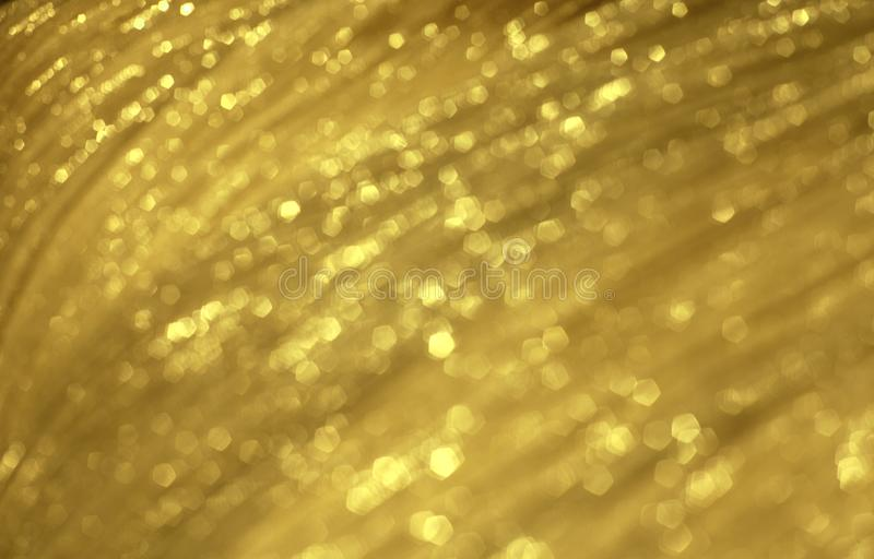 Shiny golden festive blurred tissue texture. Abstract glowing backdrop. stock photos