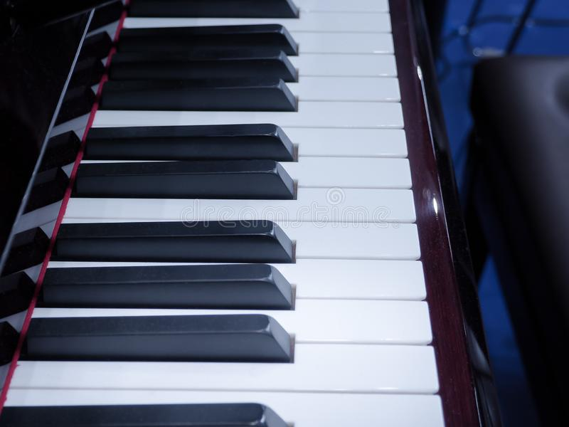 Shiny grand piano ebony and ivory keys. Details of a keyboard of a piano. royalty free stock image