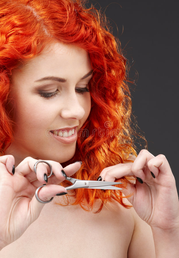 Shiny hair. Picture of lovely redhead with scissors over grey royalty free stock images