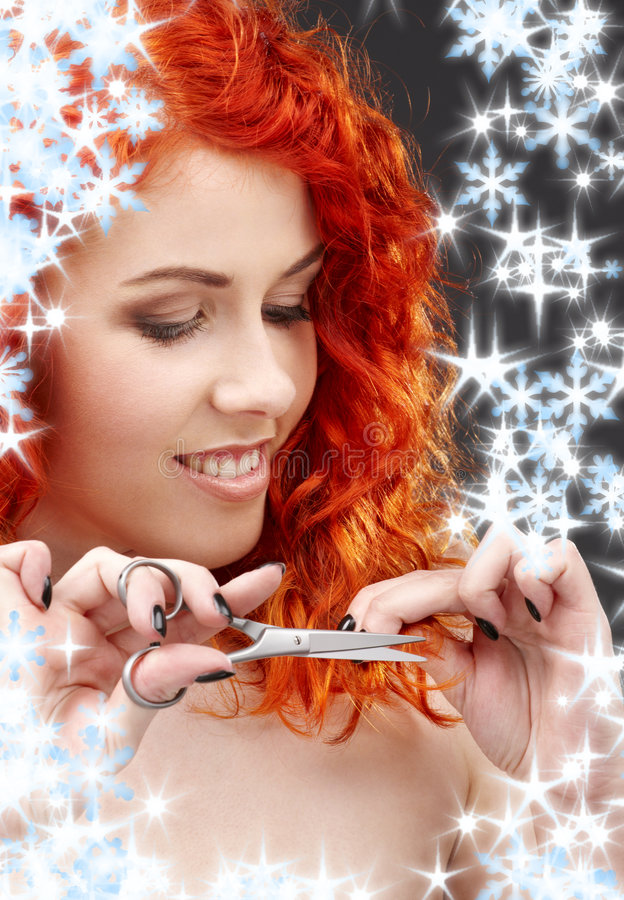 Shiny hair. Picture of lovely redhead with scissors and snowflakes royalty free stock images
