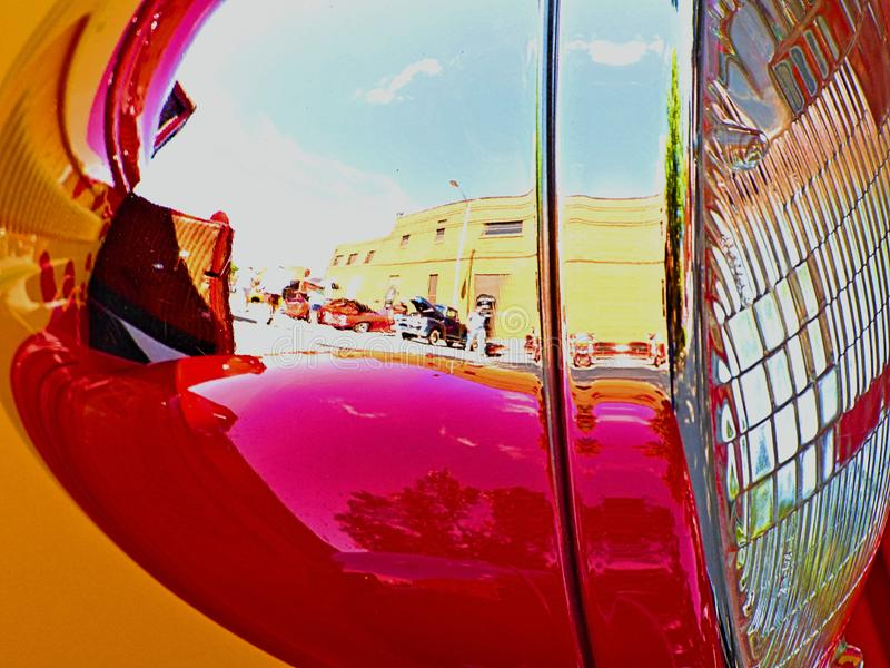 Shiny headlight of a restored automobile reflecting the buildings of historic downtown Sapulpa Oklahoma on Route 66. royalty free stock photos