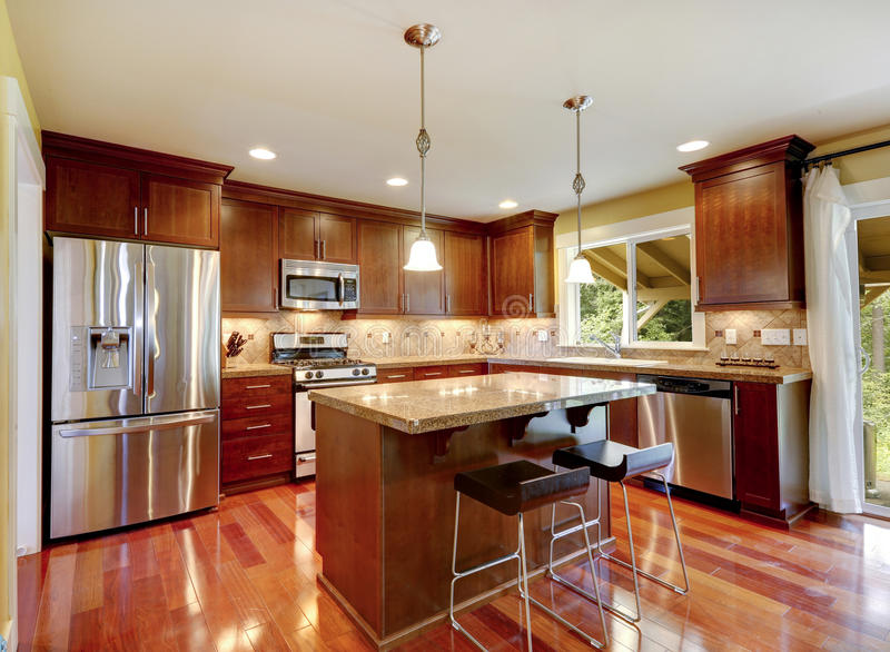 Shiny kitchen room with granite tops and steel appliances. Bright shiny kitchen room with granite tops, tile back splash trim and steel stainless appliances stock photo