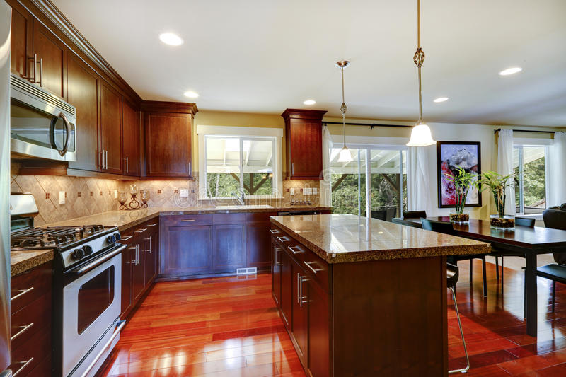 Shiny kitchen room with granite tops and steel appliances. Bright shiny kitchen room with granite tops, tile back splash trim and steel stainless appliances royalty free stock photography