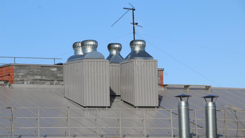 Shiny metal air ventilation on roof rotates to clean  air in  building and regulate  temperature stock photo