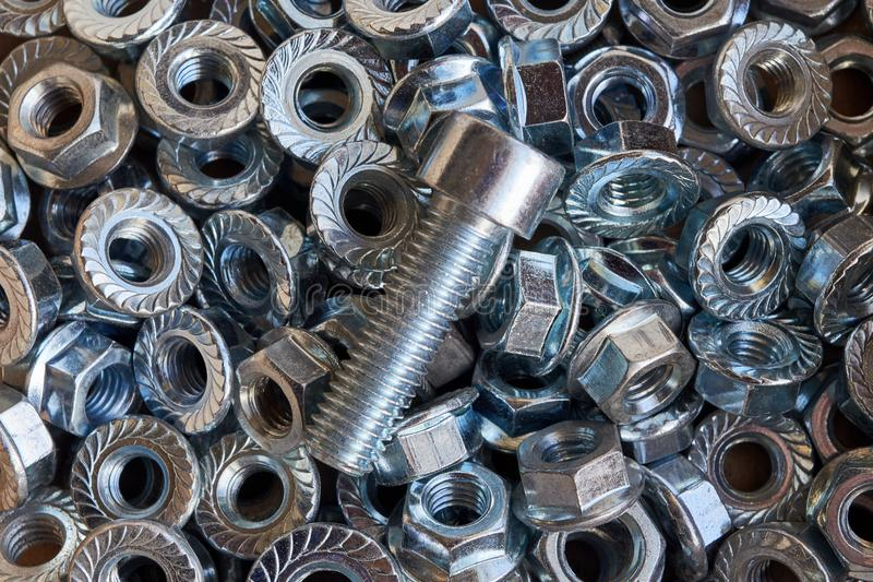 Shiny metal bolt lying on a pile of scattered nuts. Abstract background for industry from the new shiny nuts. Bolt and nuts for fixing. Chaos and confusion royalty free stock images