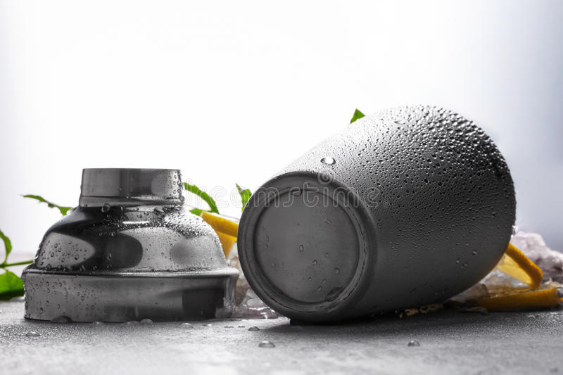 Shiny metal cocktail shaker on a gray background. Opened gray container on a gray table. A jar for making cocktails. A close-up picture of a cocktail mixer with royalty free stock image
