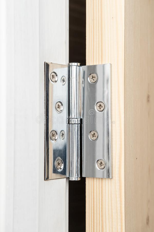Shiny metal hinge on the wooden door, part of which is painted white, and the other not. Home repair. royalty free stock images