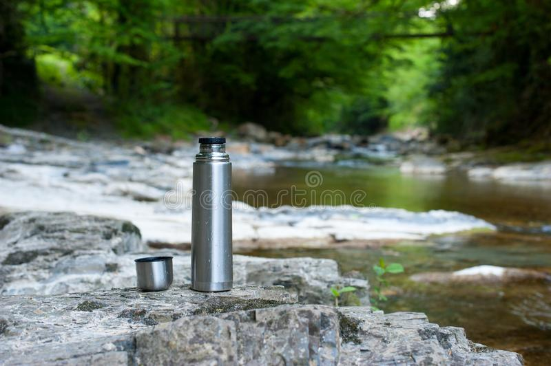 A shiny metal tourist thermos stands on the stony bank of a mountain river stock photo