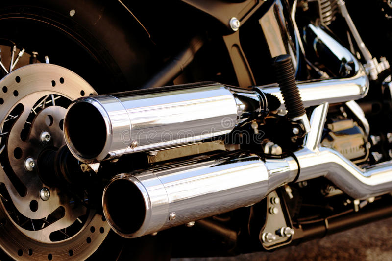 Shiny motorcycle double exhaust pipe. Side view of powerful yet elegant motorcycle, including wheel discs, double exhaust barrels, and engine components royalty free stock photo