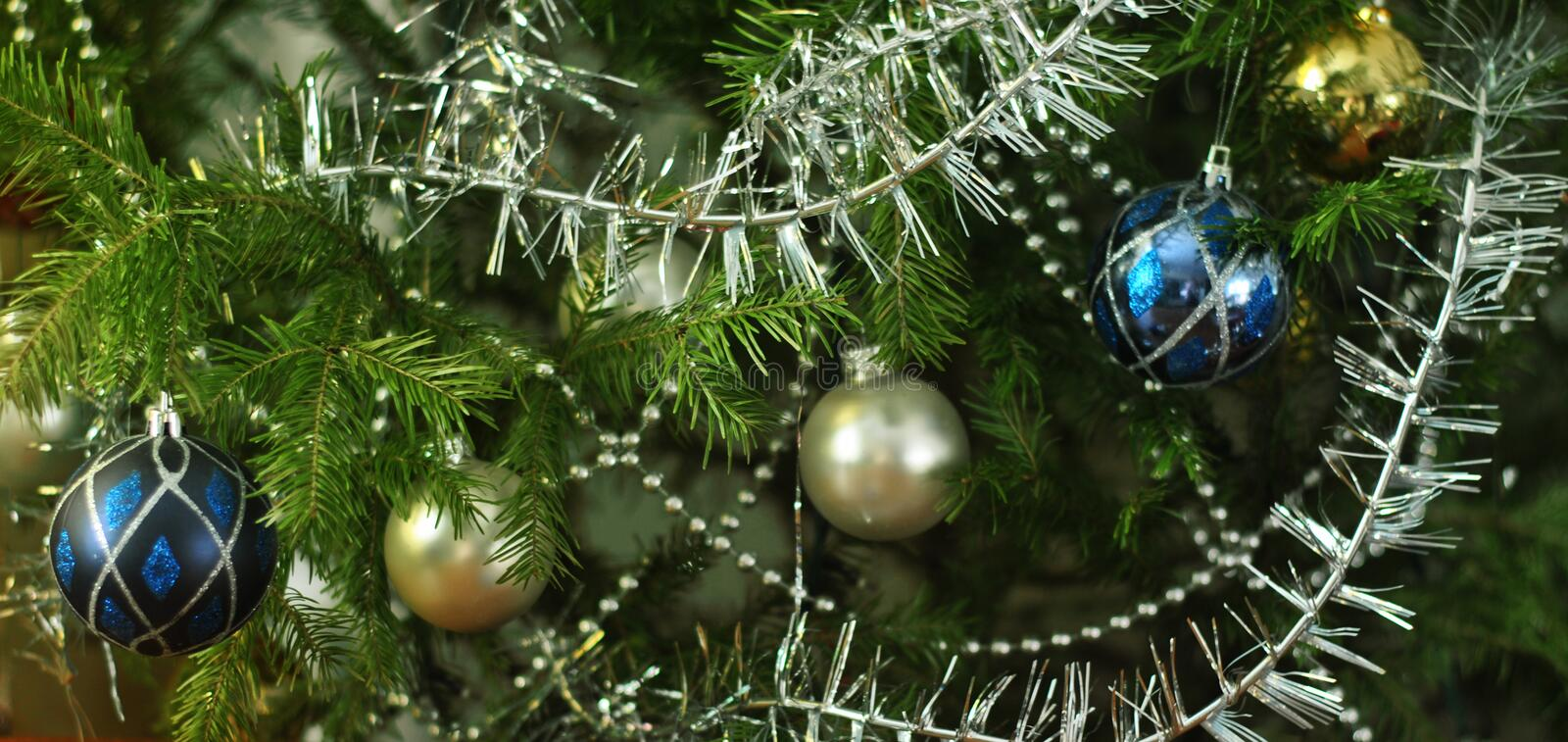 Shiny multi-colored glass balls, tinsel and beads on green spruce branches. Close-up. Shiny multi-colored glass balls, silver tinsel and beads on green spruce royalty free stock photo