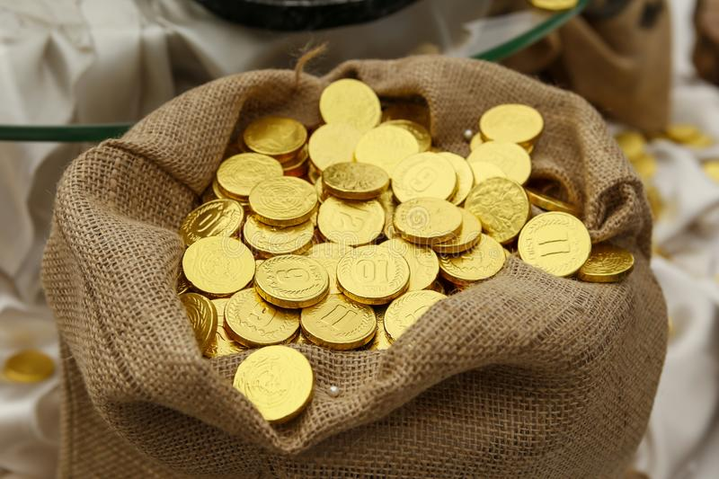 Shiny new gold coins in hessian sack stock image