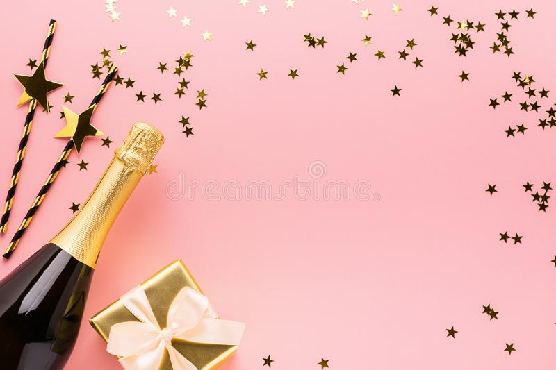 Shiny paper straws bottle of champagne wine gift with satin bow on pastel pink background. Copy space place text design. stock photo