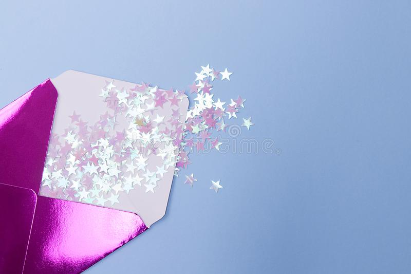 Shiny pink envelope with glitter confetti in a form stars on a blue background. Festive concept stock images