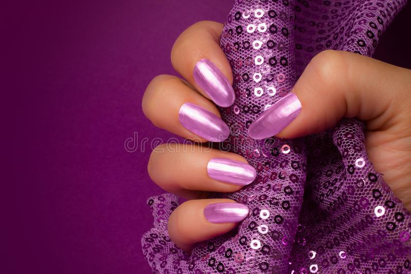 Shiny purple nails manicure. Female hand with shiny purple nails is holding purple glittered fabric on purple background, nail care and manicure concept stock image