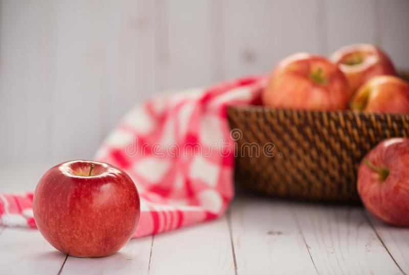 A shiny red apple sits on a wood top. Additional apples and a re. D plaid dish towel in a basket in background royalty free stock photo