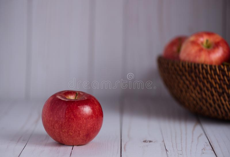 A shiny red apple sits on a wood top. Apples in basket in background. royalty free stock images