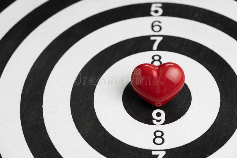 Shiny red heart shape on center of archery black and white circle dartboard with score numbers, love target Valentines background royalty free stock photos