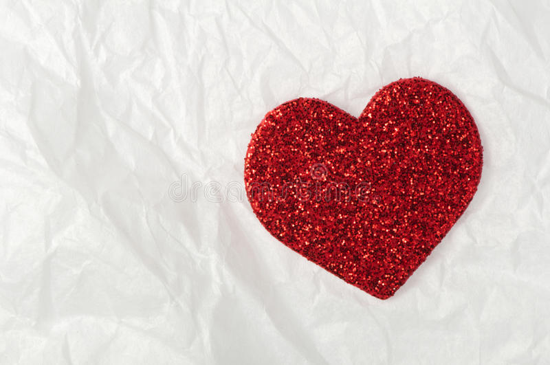 Shiny red heart on white paper royalty free stock images