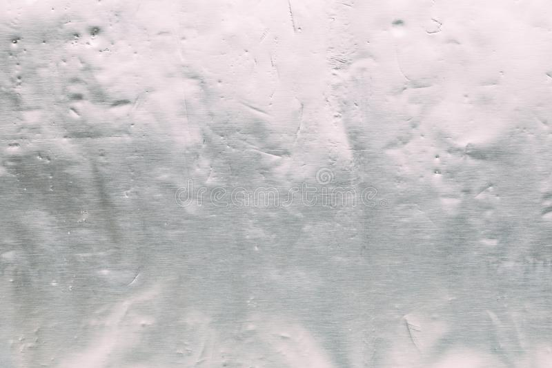 Shiny scratched silver metal texture foil for use in design as a background. Toned stock photography