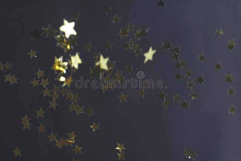 Shiny shooting stars on a dark background. Christmas decor in gold color. the view from the top stock photos
