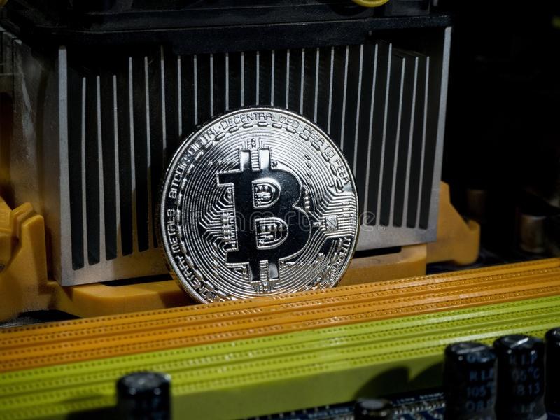 Shiny silver bitcoin virtual crypto currency coin laying on electronic circuit motherboard computer royalty free stock photos