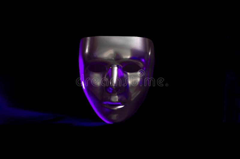 Sliver masquerade mask in shadow. A shiny silver blank masquerade mask in shadow against a black background with purple highlights creates a moody environment stock photos