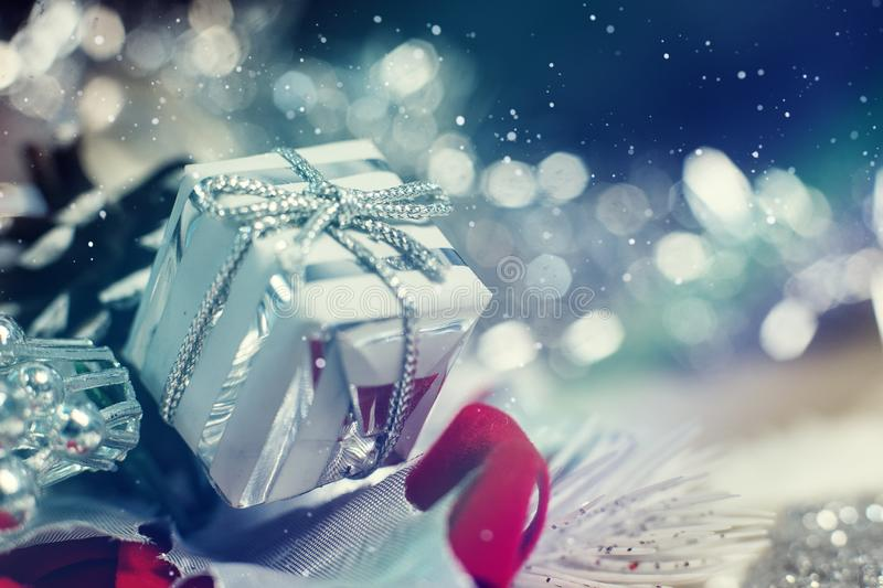 Shiny silver Christmas gift box with falling winter snowflakes. And copyspace for your greeting or wishes stock image