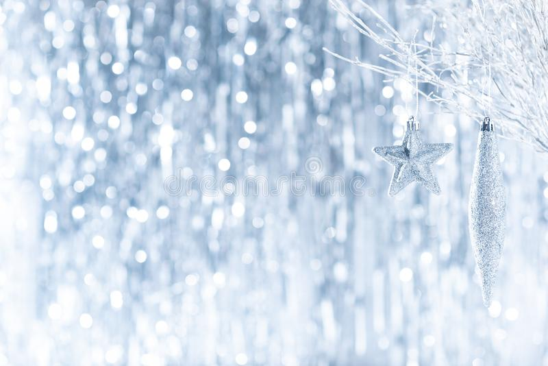 Shiny silver christmas ornaments hanging on a tree, with defocused christmas lights in the background. Christmas background. royalty free stock images