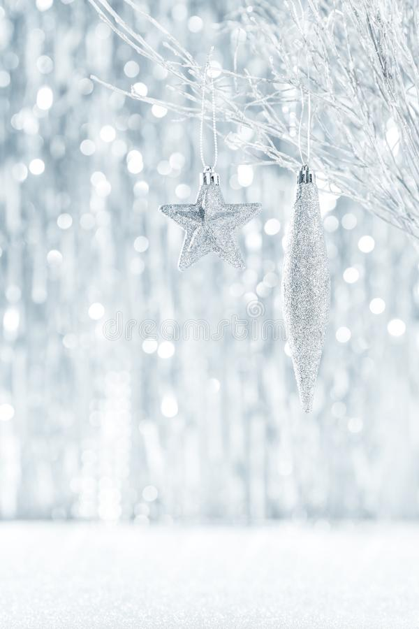 Shiny silver christmas ornaments hanging on a tree, with defocused christmas lights. Shiny silver christmas ornaments hanging on a tree, with defocused royalty free stock photos