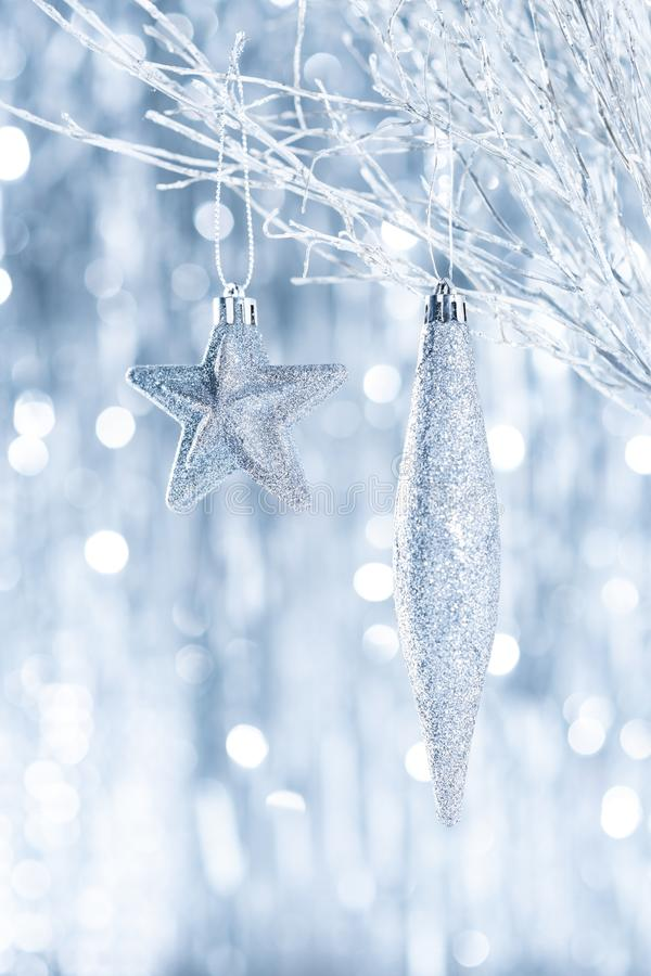 Shiny silver christmas ornaments hanging on a tree, with defocused christmas lights. stock photo