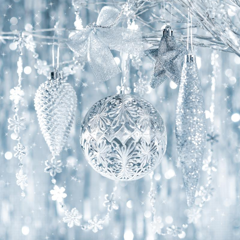 Shiny silver christmas ornaments hanging on a tree, with defocused christmas lights. Shiny silver christmas ornaments hanging on a tree, with defocused royalty free stock image