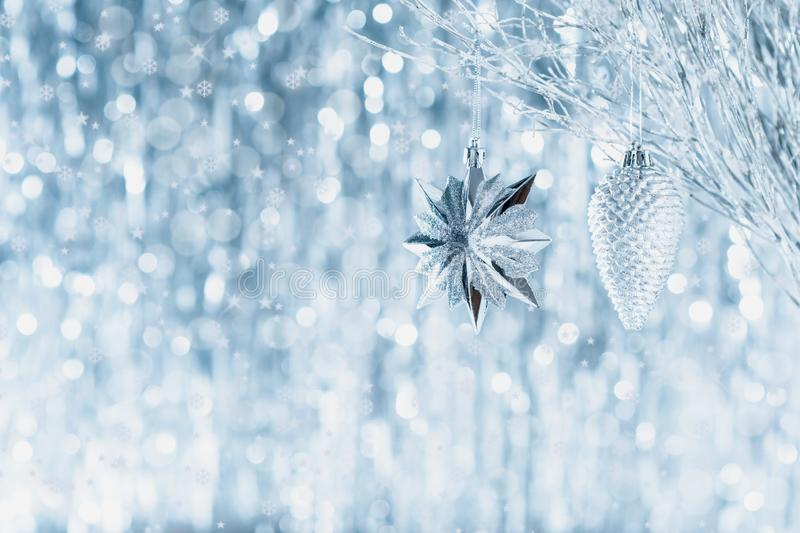 Shiny silver christmas ornaments hanging on a tree, with defocused christmas lights in the background. Christmas background. royalty free stock photos