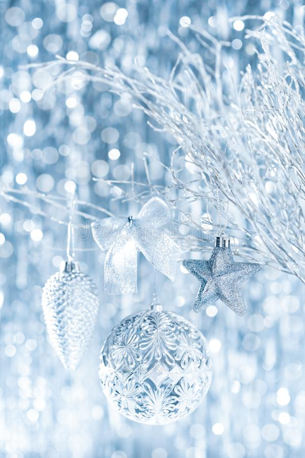 Shiny silver christmas ornaments hanging on a tree, with defocused christmas lights in the background. Christmas background. royalty free stock image