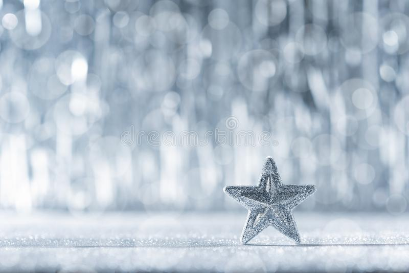 Shiny silver christmas star with defocused christmas lights in the background. Christmas background. royalty free stock image