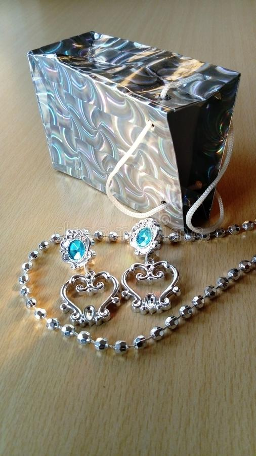 Shiny silver earrings dropped from a gift bag with blue stones. Gift for a woman on holiday.  royalty free stock photos