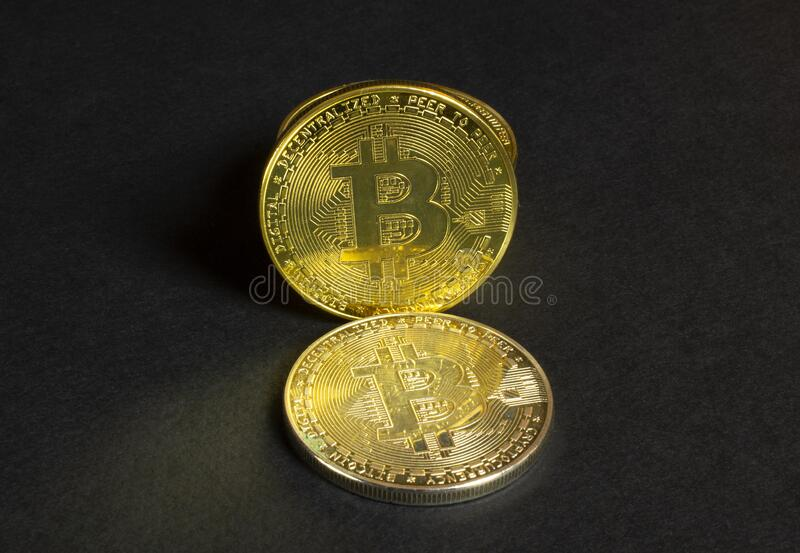 Shiny stack bitcoin coins on black paper textured background, close up view. Shiny stack bitcoin coins on black textured background, close up view stock image