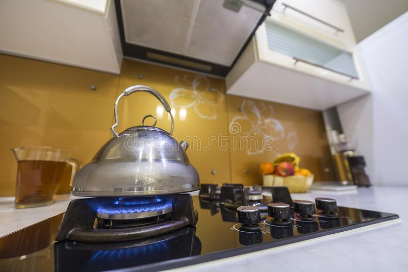 Shiny stainless tea kettle teapot with boiling water on burning gas stove on modern kitchen yellow interior background.  royalty free stock image