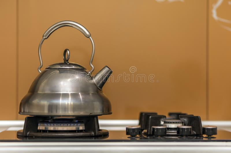 Shiny stainless tea kettle teapot with boiling water on gas stove on kitchen yellow copy space background.  stock image