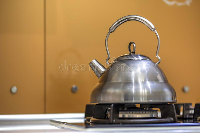 Shiny stainless tea kettle teapot with boiling water on gas stove on kitchen yellow copy space background.  royalty free stock photos