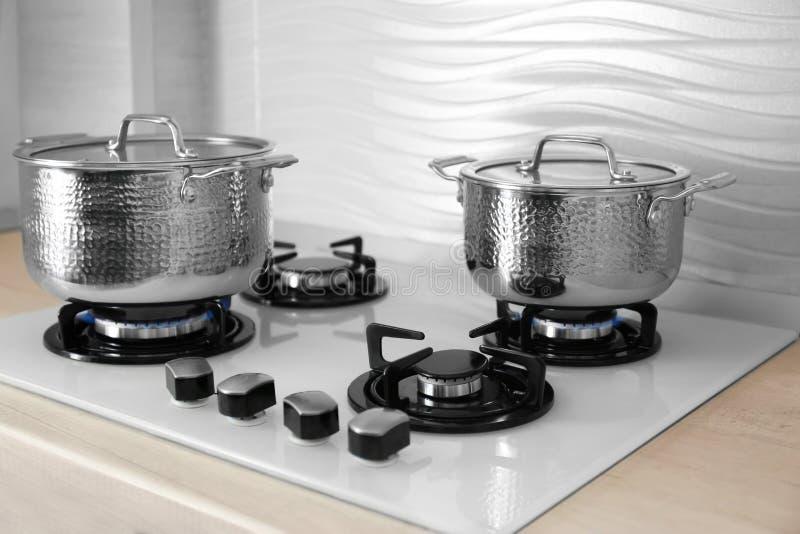 Shiny steel saucepans on gas stove stock photo