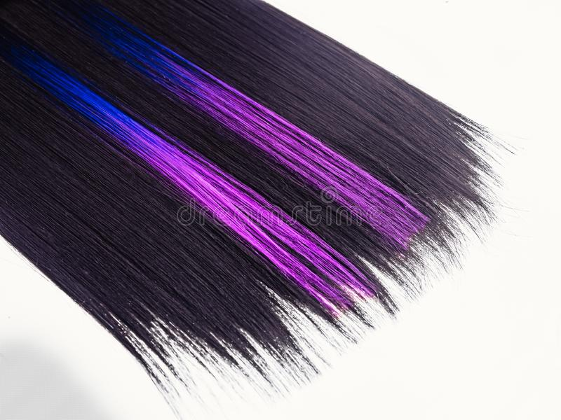 Shiny straight black hair background. Beautiful smooth brunette hair with colored purple lilac blue strands. Beauty. Trend 2019 royalty free stock photo