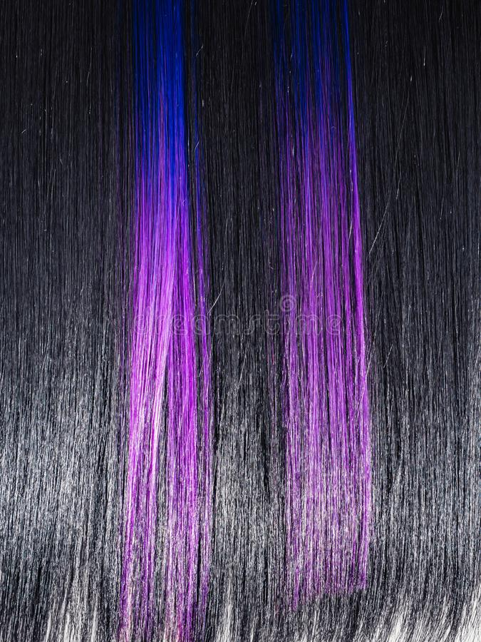 Shiny straight black hair background. Beautiful smooth brunette hair with colored purple lilac blue strands. Beauty stock photography