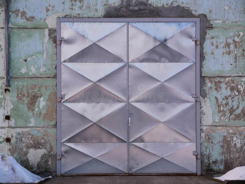 Shiny tin industrial door on old warehouse stock photos